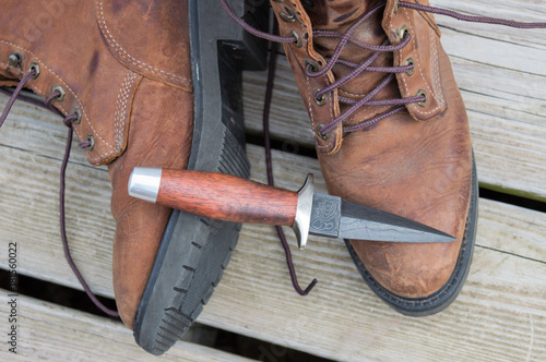 Slika na platnu A boot knife displayed on work boots.