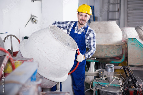 Young positive worker using concrete mixer