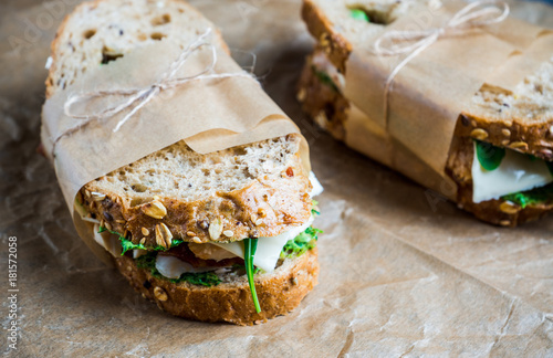 Staande foto Snack Sandwich with cereal bread, chicken, pesto and cheese on the rustic wooden background. Selective focus. Shallow depth of field.