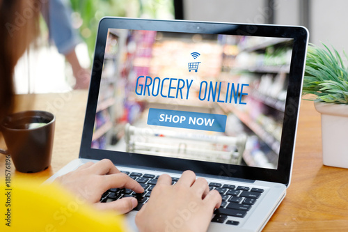 Fotografía  Woman hands typing laptop computer with grocery shopping online on screen backgr