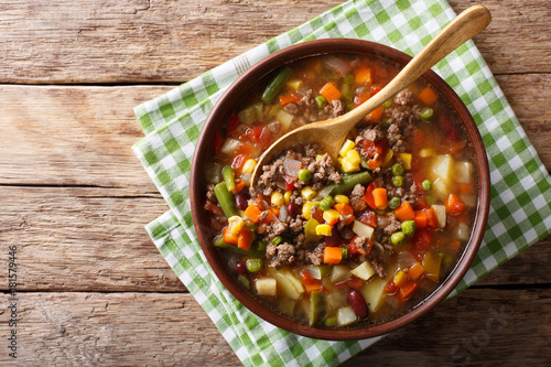 Vegetable soup with ground beef close-up in a bowl. horizontal top view
