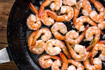 Smażone krewetki z czosnkiem na patelni, przygotowanie potrawy z owocami morza, koncepcja kuchni śródziemnomorskiej