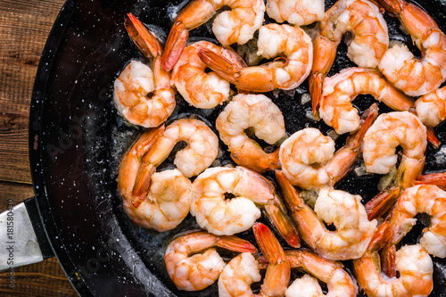 Fotografiet Fried shrimp with garlic on pan, preparing dish with seafood, mediterranean cuis