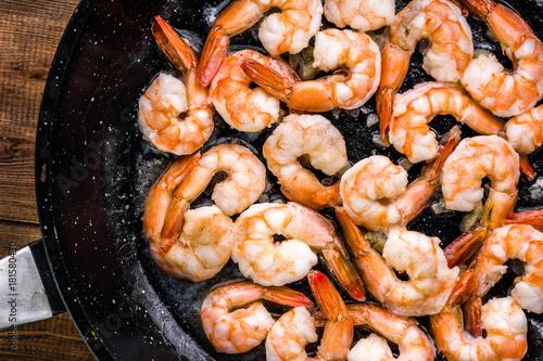 Cuadros en Lienzo  Fried shrimp with garlic on pan, preparing dish with seafood, mediterranean cuis