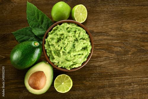 Fotografie, Obraz  Guacamole and ingredients on dark wooden background.