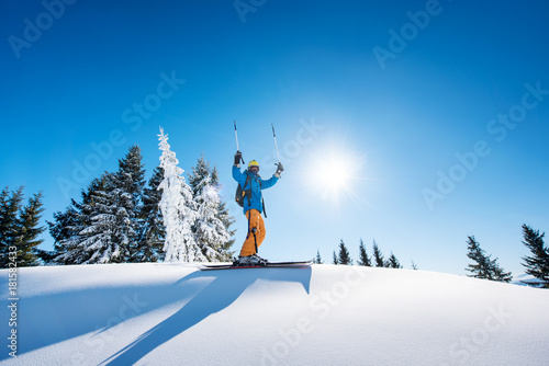 Low angle shot of a cheerful skier holding ski poles raising his arms in the air Fototapeta