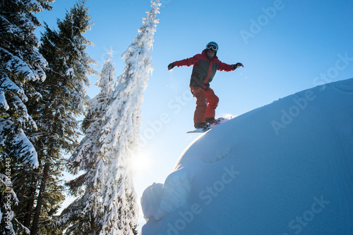 Tuinposter Wintersporten Male snowboarder riding downhill on dangerous slope in the winter mountains copyspace freeride
