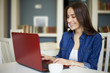 Beautiful smiling young brunette women sitting at the table and working at a laptop. Co working zone. Pretty freelancer.