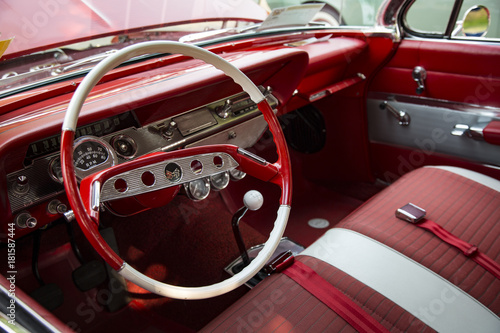 Foto op Plexiglas Cubaanse oldtimers Isolated Interior View of Restored Vintage Automobile with Red Dashboard, Red and White Steering Wheel and Fabric Seats