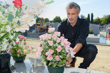 Man Putting Fresh Flowers In The Graveyard