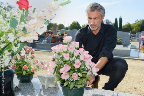 Foto op Plexiglas Begraafplaats man putting fresh flowers in the graveyard