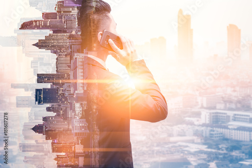 Fotografie, Obraz  The double exposure image of the business man using a smartphone calling during sunrise overlay with cityscape image