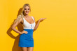 canvas print picture - Smiling Beautiful Blond Woman In Mini Dress Is Presenting