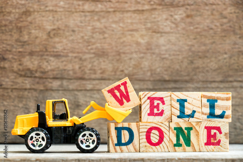 Fotografia  Toy bulldozer hold letter block w to complete word well done on wood background