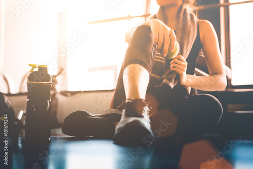 Poster Ontspanning Sport woman sitting and resting after workout or exercise in fitness gym with protein shake or drinking water on floor. Relax concept. Strength training and Body build up theme. Warm and cool tone