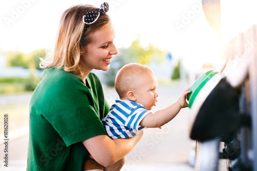 Fotografie, Obraz  Young mother with baby boy at the petrol station.