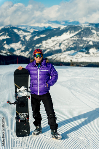 Tuinposter Wintersporten The guy is standing with a snowboard on the top of the slope