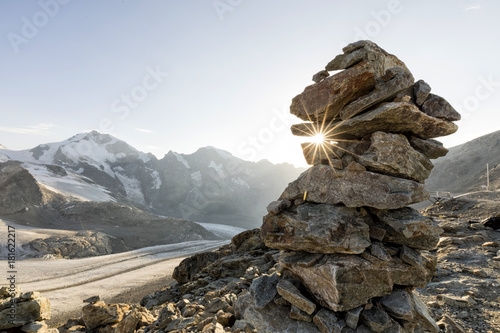 Cairn with sunray in the alps with glacier in the background, Diavolezza, Engand Fototapete