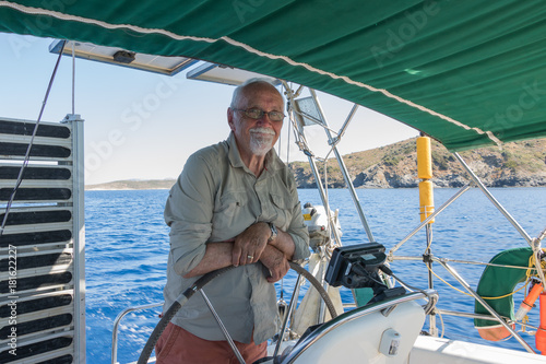 Pinturas sobre lienzo  Old man holds a steering wheel of a boat and happy smiling