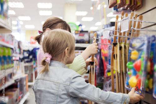 Plakat Mała dziewczynka w sklepie z zabawkami