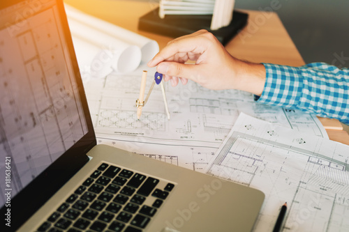 Architect working on blueprint in workplace with laptop and drawing compass Wallpaper Mural