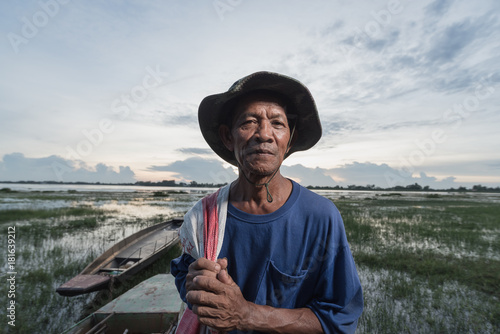 Photo portrait of the elderly native Fisher,who are out fishing in the river with boats background Wallpaper Mural