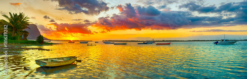 Fotobehang Oranje Fishing boat at sunset time. Le Morn Brabant on background. Panorama landscape