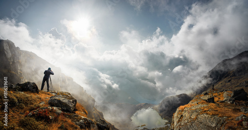 Photo sur Aluminium Gris photographer traveler with camera taking photo of mountains standin on top of a mountain and enjoying photograph