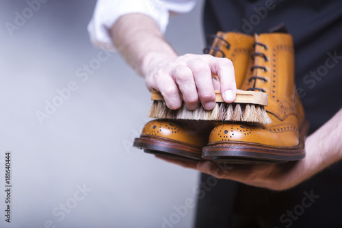 The process of cleaning shoes. A man is cleaning his shoes.