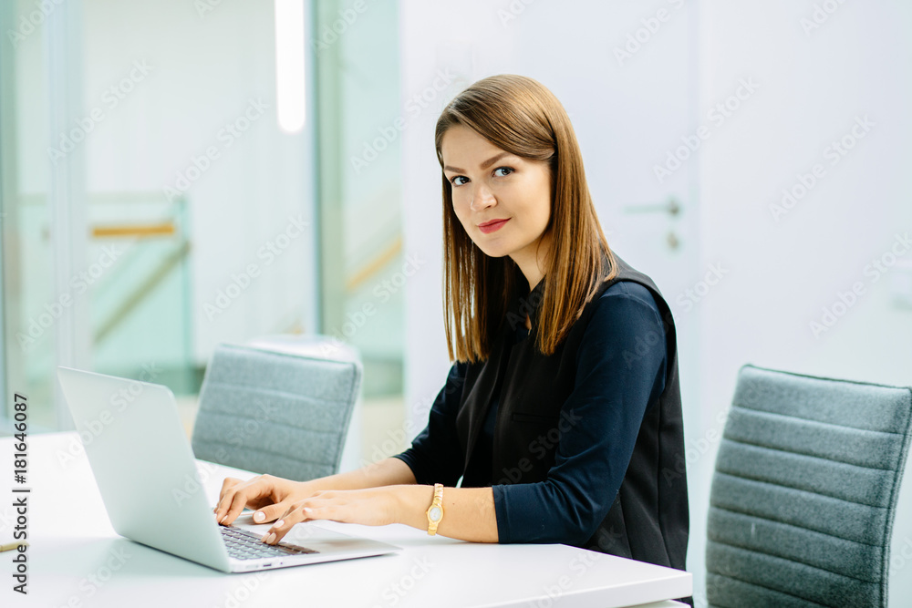 Fototapeta Image of a confident young woman sitting at working desk. Business, work and people concept.