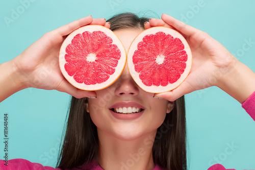 Fotografia  Pretty woman with delicious grapefruit in her arms.