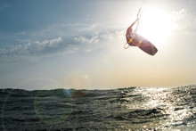 Surfer Jumping At Sunset Over ...