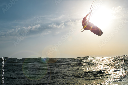 Surfer jumping at sunset over the golden sea
