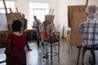 Senior woman standing by chair while artists sketching