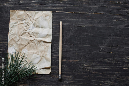 Sheet of paper on black wooden table Wallpaper Mural