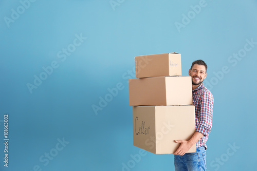 Obraz Man with moving boxes near color wall - fototapety do salonu
