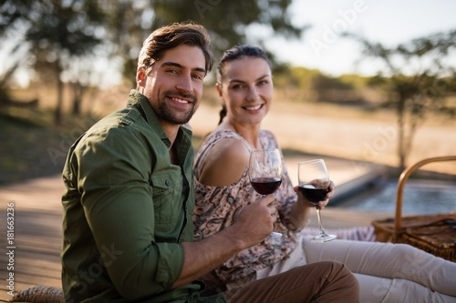 Couple having red wine during safari vacation