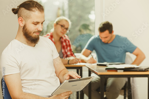 Fototapety, obrazy: Student boy with tablet in front of her classmates