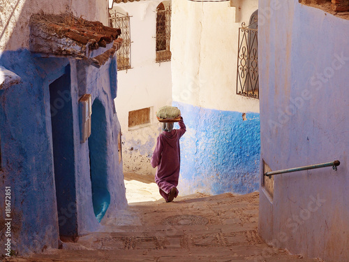 A woman caring the bread on her head and walking down the blue-white streets in Chefchaouen - the blue city Morocco - amazing palette of blue and white buildings