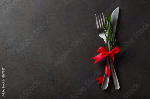 Festive set of cutlery knife and fork with red satin bow with rosemary, dark stone slate background, top view, copyspace, horizontal image
