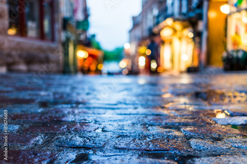 Valokuva Macro closeup of colorful, vibrant and cobblestone street at night after rain wi