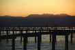 sunset over the beach. pier sea and mountains