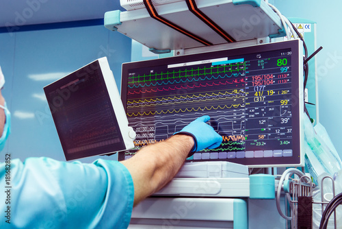 Male anaesthesiologist hand pointing vital activity data at modern monitor system in operation room Canvas Print