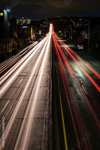 Light trails lead down the highway to the Seattle city skyline at night