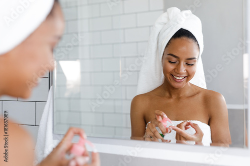 Fototapeta  Happy young woman applying face cream in bathroom, standing in front of a mirror