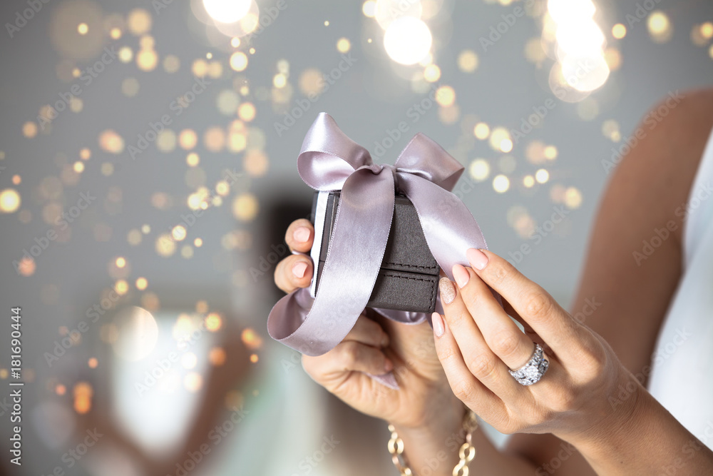 Fototapeta Close up of woman hands holding small gift with ribbon.