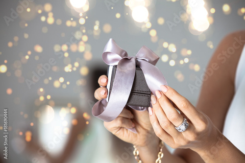 Photo  Close up of woman hands holding small gift with ribbon.