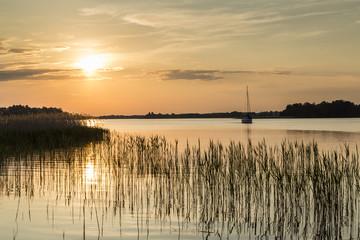 zdjęcie łódki w zachodzącym słońcu na jeziorze