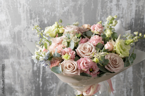 Valokuva  beautiful bouquet of mixed flowers into a vase on wooden table