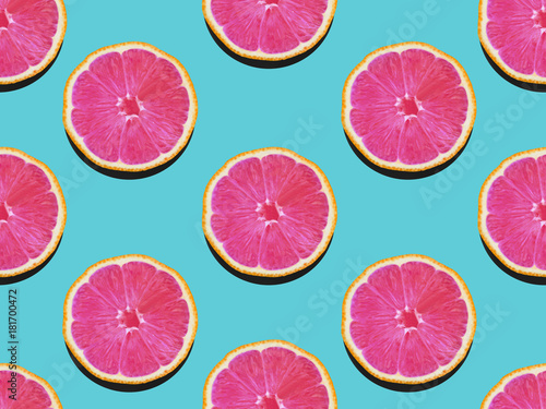 Poster Pop Art Grapefruit in flat lay Fruity pattern of grapefruit with pink flesh on a turquoise background Top view Modern flat lay photo pattern in pop art style